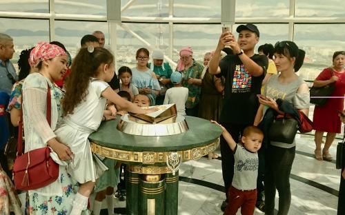 Kohalikud võtsid Beyetereki tornis rivvi, et presidendi kulda valatud käejälge katsuda.